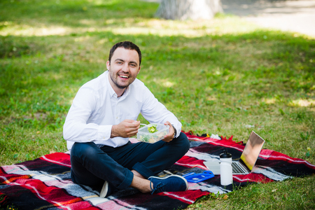 lunchtime: young business man enjoying food which he brought in a lunch box from home. Lunchtime at the park outdoors Stock Photo