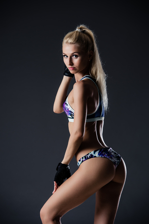 Fit girl with blonde hair wearing sporty short top, shorts and gloves standing over dark background.