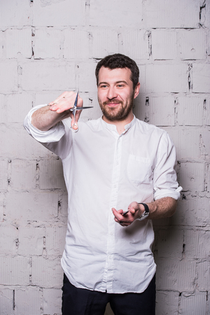 affable: Portrait of young beautiful hairdresser man wearing white shirt with scissors ongrey brick wall.
