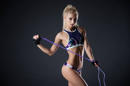 motivator: Fitness woman posing with skipping rope on a black background. Sports motivation. Perfect female fit figure. Sexy girl in the studio