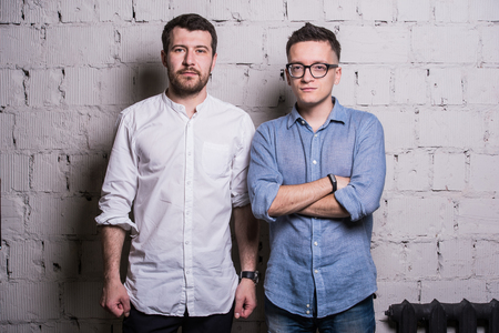 exult: Two young men startupers over grey brick wall loft interior design.