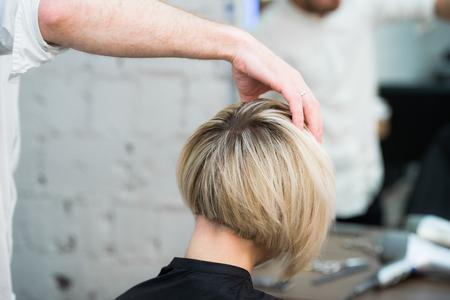 Primer retrato adolescente joven muchacha que se sienta en la silla en el salón de pelo en espejo mientras que pelo que controla su nuevo corte de pelo.