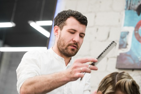 coiffeur: male hairdresser puts womans hair in a hairdressing salon.