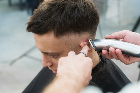 electric razor: Professional styling. Close up side view of young man getting haircut by hairdresser with electric razor at barbershop.