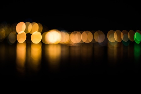 Beautiful blurred city lights with bokeh effect reflected on water background. Stock Photo