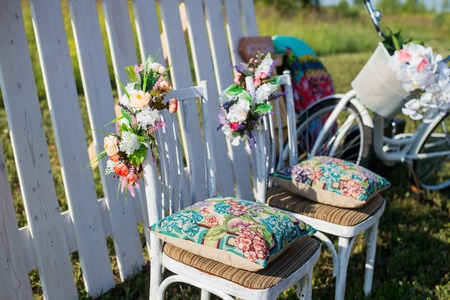 Beautiful open terrace in the garden with  coloured vintage white chairs, colorful velvet pillow and fence palisade, bicycle on background decorated flowers in boho style