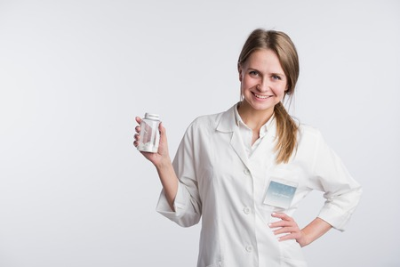 unlabeled: Young female doctor presenting a white unlabeled bottle or recipient of pills.