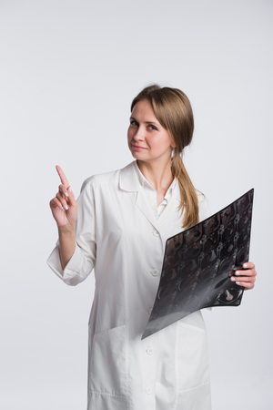 women s health: Doctor holding a X-ray and pointing to blank copy space, white background.