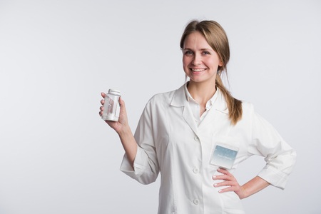 Portrait of a young pharmacist showing pills. Stock Photo