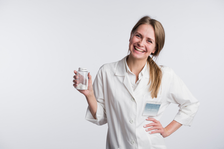 recipient: Young female doctor presenting a white unlabeled bottle or recipient of pills.