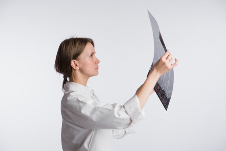 backview: A female doctor examining an x-ray picture, back-view. Stock Photo