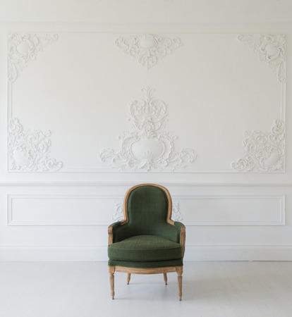 grecas: Antique green armchair fretwork wall on backround Foto de archivo