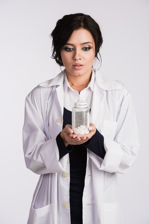 Beautiful young brunette female nurse or physician in blue dress and white lab coat holding a bottle of pills.