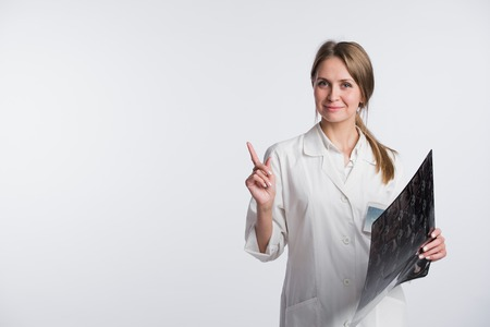 Doctor holding a X-ray and pointing to blank copy space, white background.