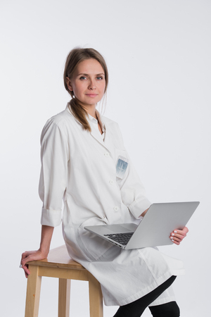 a lady doctor: Smiling female doctor working on her laptop against a white background. Stock Photo