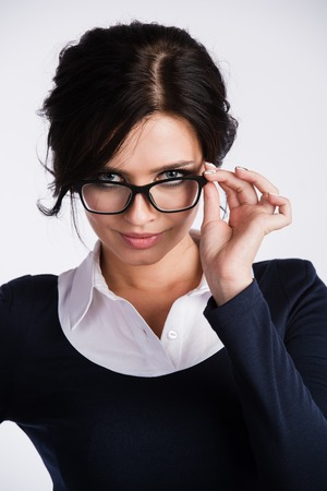 hesitations: Young business woman looking skeptically over her spectacles, over white background.