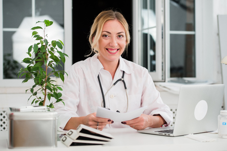 mid adult female: Mid adult female doctor reading documents at office desk.