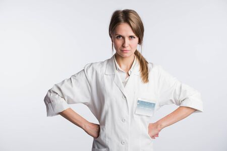 stringent: Portrait of Woman surgeon doctor in confident pose isolated over white background with hands on hips.
