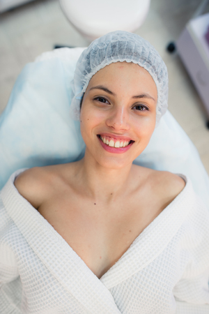 resurfacing: beautiful patient smile lying on bed in surgery room hospital. Stock Photo