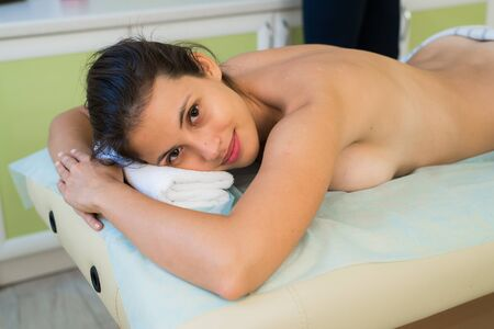 Portrait of a smiling beautiful woman ready for massage at beauty spa.