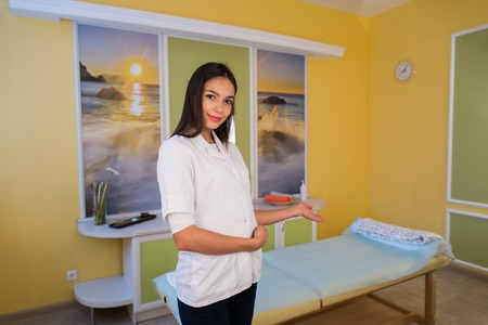 beauty therapist: Smiling beauty therapist standing beside massage table at the spa and welcomes invites customer.