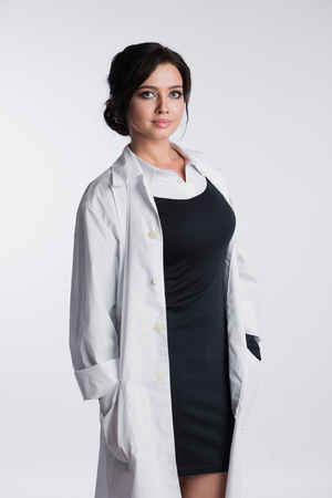 Woman doctor holding up her collar and standing against a white background. Stock Photo