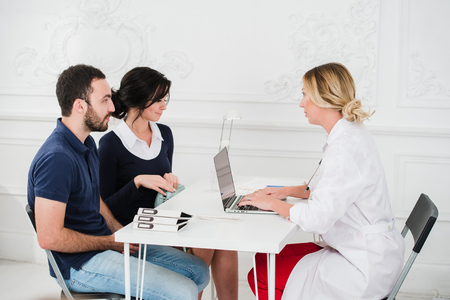 doctor burnout: Doctor and young couple patients at office. Stock Photo