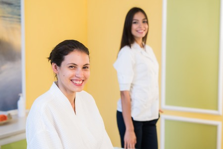 cosmetologist: Woman beautician doctor with patient in spa wellness center. Young female professional cosmetologist made massage to beautiful brunette girl in cosmetology cabinet or beauty parlor Stock Photo