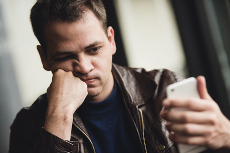serious guy: Portrait of tired young businessman typing on cellphone at cafe. Stock Photo