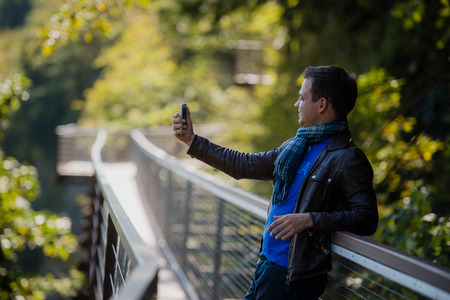 Young fashionable Hispanic man taking a selfie outdoors on sunny summer day. Modern lifestyle concept Stock Photo
