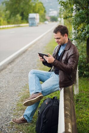 Man sitting on a road fence with gps on tablet pc and using online maps.