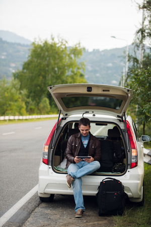 man searching: leisure, road trip, travel and people concept - happy man searching location using tablet with online map sitting on trunk of hatchback car outdoors. Stock Photo