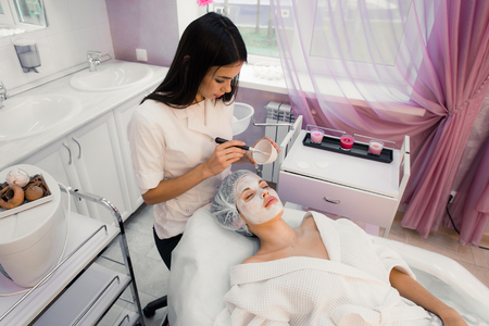 facemask: Portrait of young woman while facial cosmetic procedure in spa salon.
