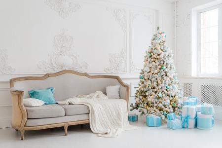 Stijlvol kerstbinnenland met een elegante sofa. Comfort thuis. Kerstboom met cadeaus geschenk onder in de woonkamer.