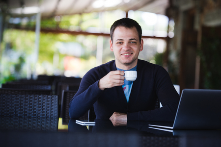 No minute without my laptop. Handsome young man working on laptop and smiling while enjoying coffee in cafe Stock Photo