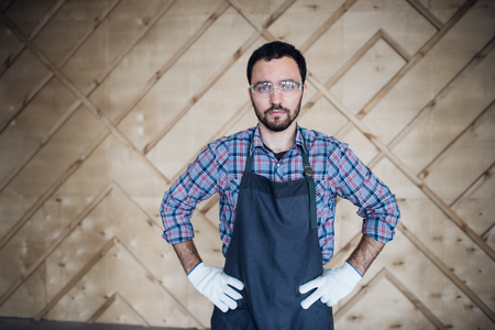 Young carpenter wearing gloves and glasses with hands on hips. Stock Photo