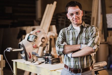 rolledup sleeves: Handsome carpenter in protective glasses is looking at camera and smiling while standing near his wooden object in the workshop.