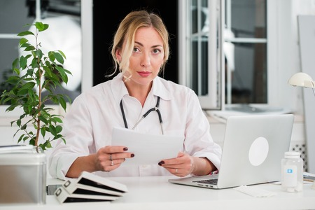 Mid adult female doctor reading documents at office desk.