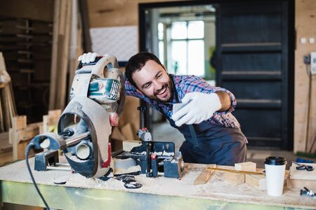 Carpenter taking a selfie with miter saw at his work place. Stockfoto
