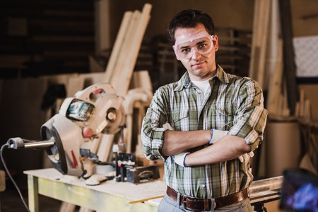 Handsome carpenter in protective glasses is looking at camera and smiling while standing near his wooden object in the workshop.