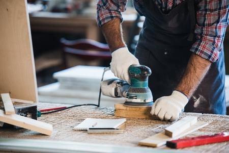 労働者は、アンギュラー研削盤の木を磨きます。 写真素材
