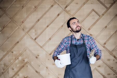 Man with tin of paint and brush looking up. Stock Photo