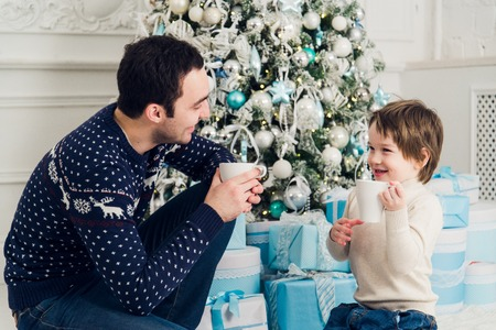Happy dad and son with cups of tea talking near Christmas time at home.