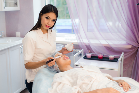 a lady doctor: Young beautiful woman having spa procedure on her face.