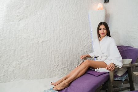 Mujer en sala de sal. Joven y bella mujer en bata de baño relajante en la sala de sal. Foto de archivo - 68969183