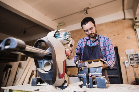 cut off saw: Framing contractor using a circular cut off saw to trim wood studs to length