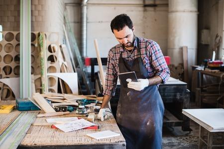 デジタル タブレットを押し彼の木工スタジオで立っている大工の肖像画。 写真素材