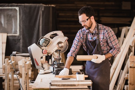 profession, carpentry, woodwork and people concept - carpenter with wood plank and notebook checking his notes at workshop Stock Photo