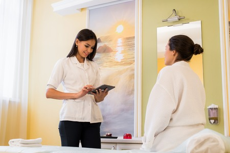 Cosmetic consulting, direct sale. Two women in wellness salon dressed in white robes.