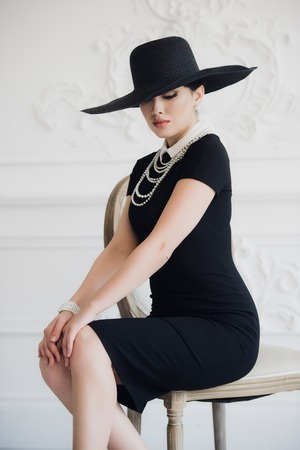 Elegant woman in black dress with a hat sitting on a chair. Stock Photo